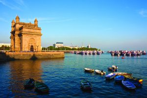 Gateway of India in Mumbai during sunset.  There are several small boats in blue water and a castle-like building towards the left.  There is land visible in the distance.